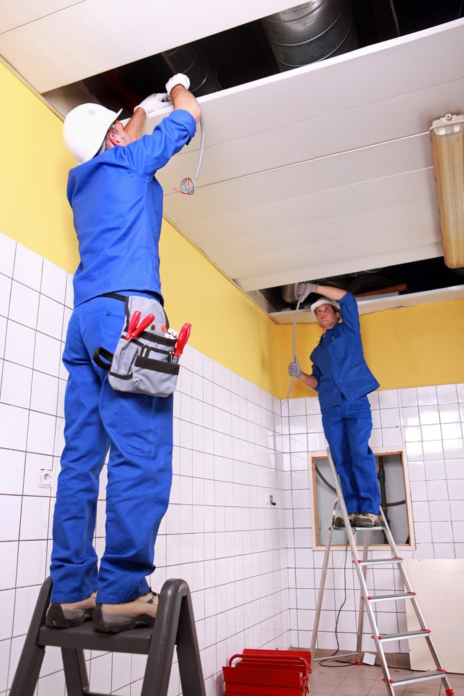 Electricians at work on ladders working in a ceiling space