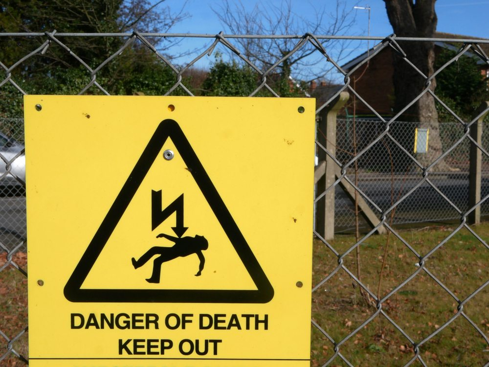 A sign on a chain link fence warning of the risk of death due to electricity