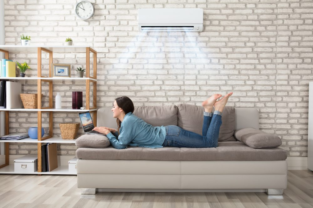 Woman lying on couch using a laptop enjoying air conditioner