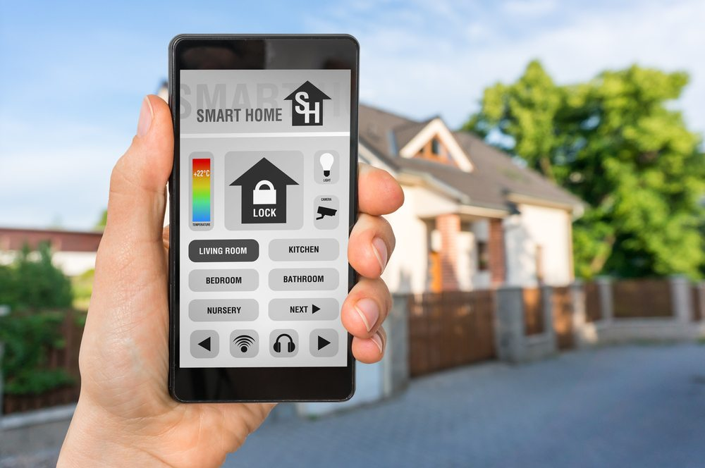 A smart phone with a smart home app on the screen and a house in the background