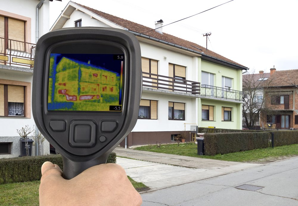 A thermographic camera in front of a house showing a thermograph.