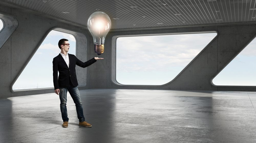 Male presenting large light globe as bright idea
