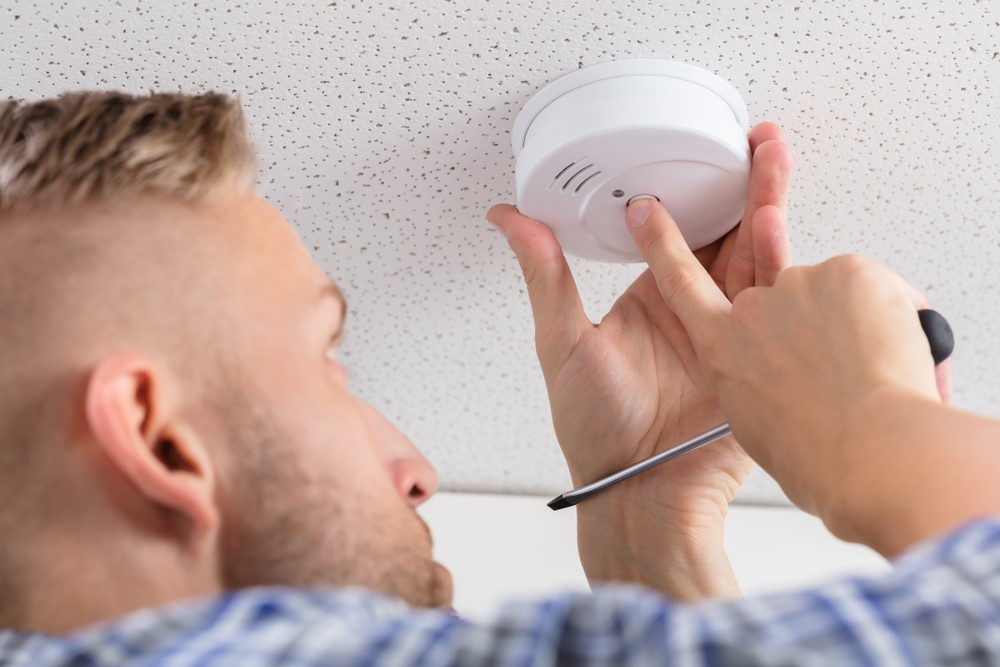 Installing Smoke Detector on Ceiling Wall at Home
